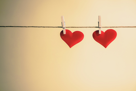 Two adorable red hearts side by side hanging from a string by wooden pegs. Romantic Valentines Day with copy space. Stok Fotoğraf