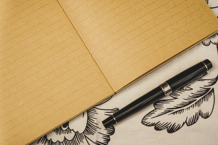 Beautiful fountain pen next to kraft notebook, on white floral tablecloth. Copy space for special event or occasion.