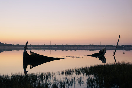 Broken down and sunken boat close to the shore of the Aveiro Lagoon, on a sunset.