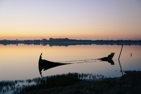 Broken down and sunken boat close to the shore of the Aveiro Lagoon, on a sunset. With water reflections. Stock Photo