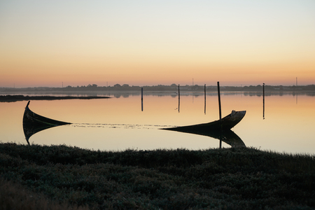 Weathered and sunken boat in the Aveiro Lagoon, on a sunset.