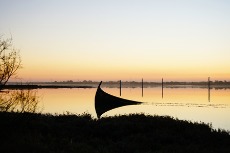 Abandoned and sunken boat in the Aveiro Lagoon, on a sunset.