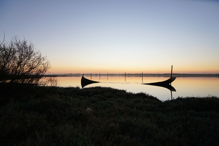 Damaged and sunken boat close to the shore in the Aveiro Lagoon, on a sunset. Stockfoto