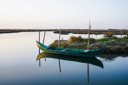 Weathered small boat close to shore in peaceful and beautiful lagoon on bright day. Boat reflection on water. Stockfoto