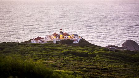 Lighthouse of the Cabo Mondego surrounded by vegetation and the sea, seen from the distance. Stockfoto