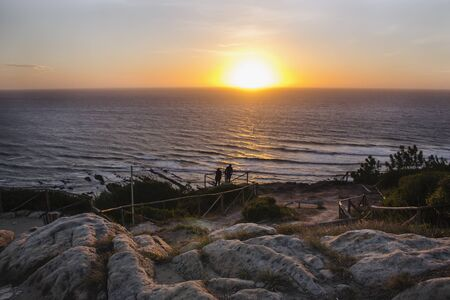 Gorgeous view of the sea with dramatic sunset, seen from a lovely and rocky viewpoint in Cabo Mondego, in Portugal.