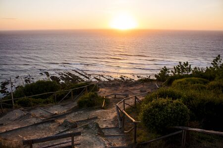 Amazing view of the sea during sunset, seen from a lovely and rustic viewpoint in Cabo Mondego, in Portugal.