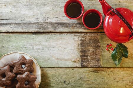 Flat lay of rustic wooden table with star chocolate cookies in ceramic plate, red teapot and cups. With copy space.