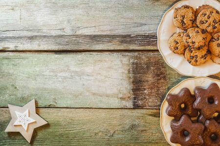 Flat lay of rustic wooden table with chocolate chip and star-shaped cookies in ceramic plates. With copy space.