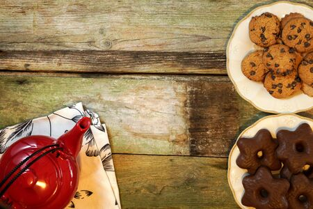 Rustic wooden table with cookies and tea. Red teapot on top of white cloth and chocolate chip cookies. With copyspace.