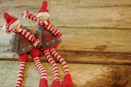 Pair of adorable and cute Christmas Elves - boy and girl - sitting in rustic wooden table. With copy space.