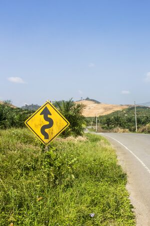 Yellow double curve sign next to a deserted asphalt street. Road trip travel concept. In Phang Nga, Thailand