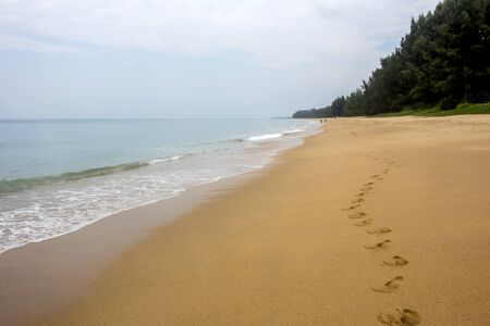 Seascape with row of footprints in golden sand at an almost deserted Mai Khao beach in Phuket, Thailand Stockfoto