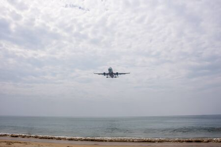 Plane over Nai Yang beach almost landing in Phuket airport during a cloudy day, with small waves crashing into sand Stockfoto