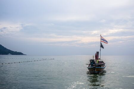 Long-tail boat docked in Kata beach, with Thai flag flapping in the wind, during a cloudy day. In Phuket, Thailand