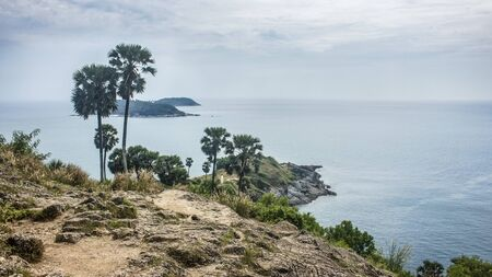 Beautiful landscape of the Promthep Cape, with palm trees and the Andaman sea in a cloudy day. With copy space.