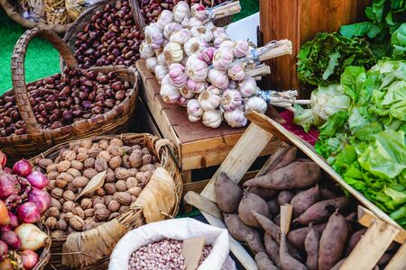 Organic vegetables in wicker baskets and wooden crates at Farmers Market. Garlic, sweet potatoes, walnuts and chestnuts.