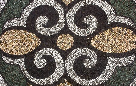 Horizontal photo of the traditional Balinese pebble stone stonework on pavement - usually in gardens - in Bali, Indonesia