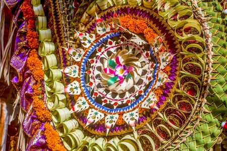 Balinese colorful and festive wedding craft decoration with coconut leaves, flowers and fabric.
