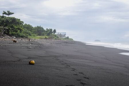 Horizontal photo of the seaside seascape of Pantai Wates. Footprints and a coconut shell lying in the black sand beach with hut in background on a cloudy day