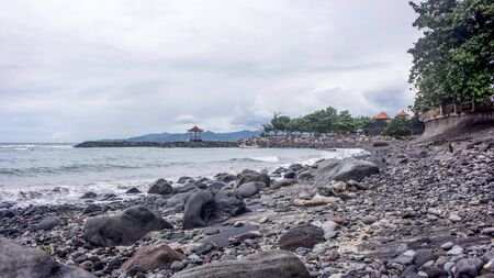 Horizontal photo of Candidasa rocky beach in Bali, Indonesia, during a cloudy day. Trees and traditional Balinese gazebo in the background