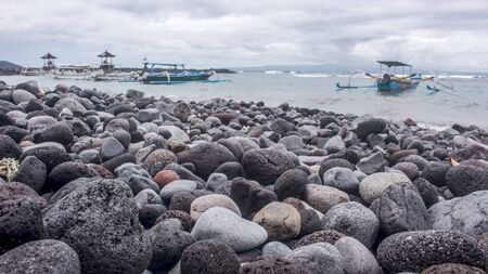 Horizontal photo of a stone beach and traditional Balinese fishing boats and gazebos in the distance in pantai Candidasa beachfront, during a cloudy day. Bali, Indonesia Stockfoto