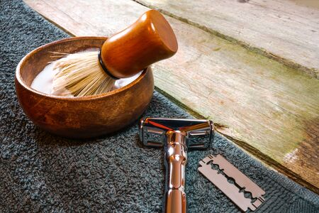 Shiny safety razor, shaving brush and lather in bowl. Wet shaving in rustic wooden table, with copy space.