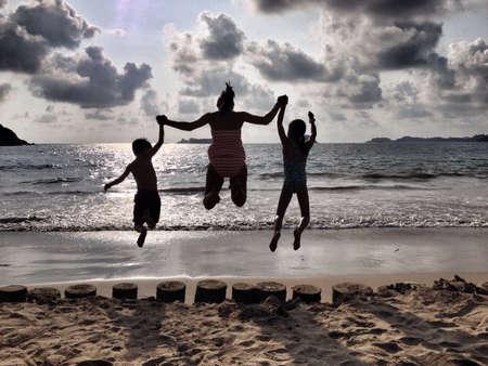 Moeder en kinderen silhouetten springen van vreugde op het strand