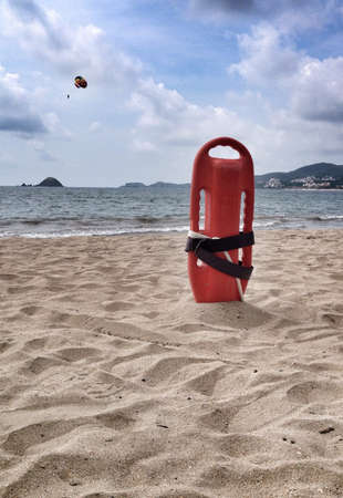 Lifeguard buoy standing on beach with parachute on the back 版權商用圖片
