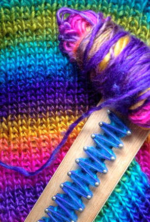 Wood loom with yarn and knitted scarf, rainbow pattern Stok Fotoğraf