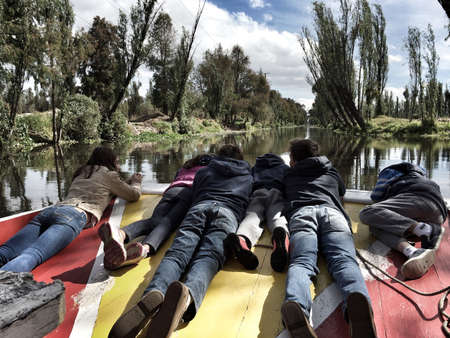 laying down: Teens and kids laying down at the front of a small boat enjoying the ride