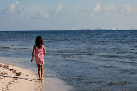 waterline: Little girl walking in the waterline at seashore seeing from behind Stock Photo