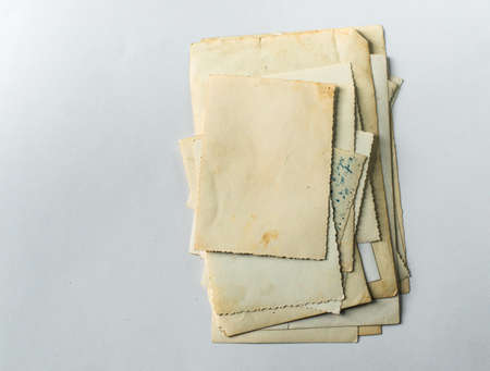 Folded old photos on a white table. Postcard rumpled and dirty vintage. Retro postcard