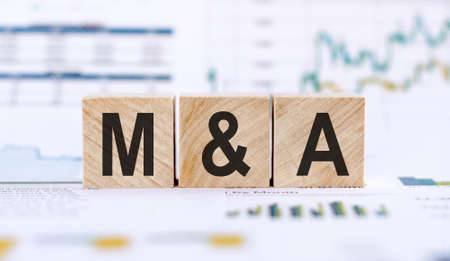M and A or Merger and Acquisition made with wood building blocks on background from financial graphs and charts