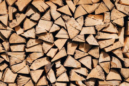 Firewood for your design, Background of dry chopped firewood in a pile