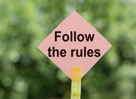 Follow the Rules written on a piece of pink paper on notes on a green background. Copy space for your design