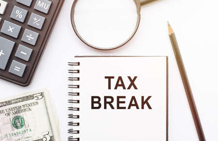 The phrase Tax Break in notebook with calculator, magnifier, money and pen background on white table. Business and financial concept