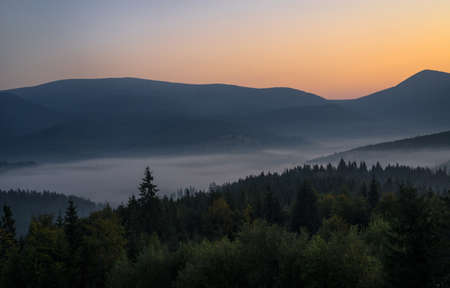 Smoky mountain landscape with mountain and light rays before sunrise.