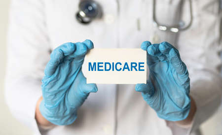 Doctor holding a card with Medicare, medical concept Standard-Bild
