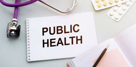 PUBLIC HEALTH CONCEPT Text, On Background of Medicaments Composition, Stethoscope, notebooks. medicine