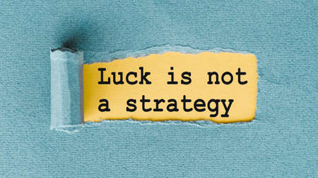 The text LUCK IS NOT A STRATEGY. On torn turquoise paper with yellow background