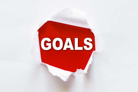 White torn paper with red background and a word GOALS 版權商用圖片