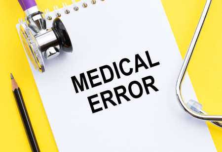 text MEDICAL ERROR write on a medicine card. Medical concept with a stethoscope on a yellow background