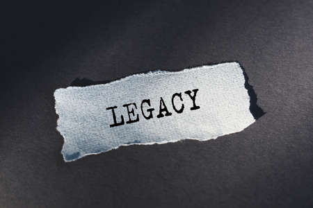 Legacy text, inscription, phrase is written on a torn paper that lies on a dark table. Business concept.