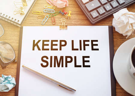 Conceptual hand writing showing Keep life Simple. Business photo showcasing ask something easy understand not go into too much detail. Paper on office table with coffee, sticky papers, pen and calculator