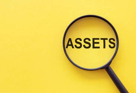 The word assets through a magnifying glass on a yellow table. Financial Accounting. Money concept.
