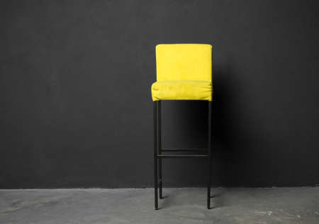 High bar stool against a dark gray wall. Stylish chair in loft style, in classic interior