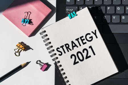 Strategy 2021 - a text written in a notebook lies on a laptop with office supplies. A forward-looking approach to achieving sustainable competitive advantage, looking for new opportunities in business and education.