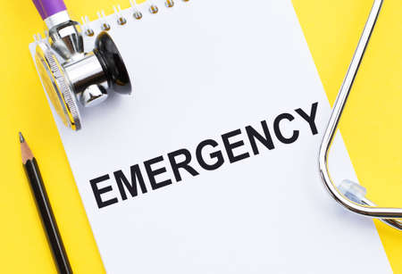 The word EMERGENCY is written on a medical notebook next to a stethoscope.