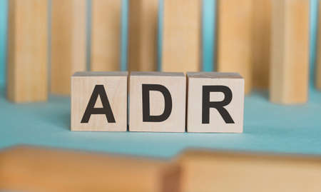 The abbreviation ADR (Adverse Drug Reaction) is written on wooden blocks against a light blue background. Medical concept.